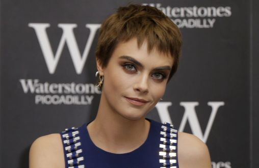 Model and actress Cara Delevingne poses for photographers prior to a book signing of copies of her debut young adult novel 'Mirror, Mirror' in a bookstore in London, Wednesday, Oct. 4, 2017